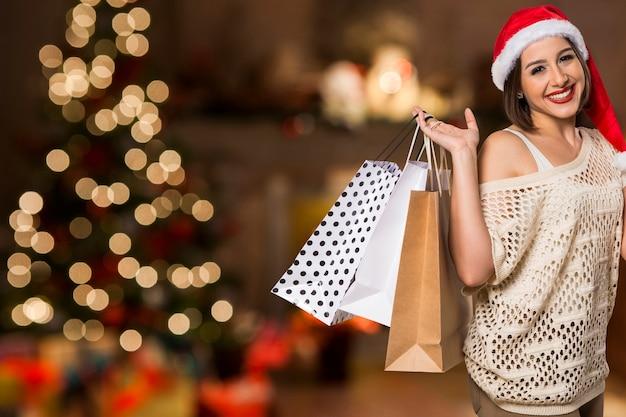 Рождественский портрет женщины держа хозяйственные сумки. улыбается счастливая женщина над боке рождественские огни