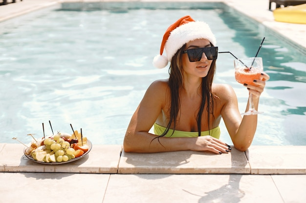 Christmas woman relaxing by the swimming pool. funny girl celebrating christmas in a resort. with cocktail and fruits.