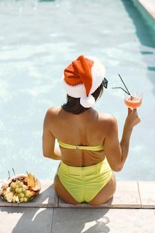 Рождественские женщина расслабляющий бассейн. смешная девочка празднует рождество на курорте. с коктейлем и фруктами.