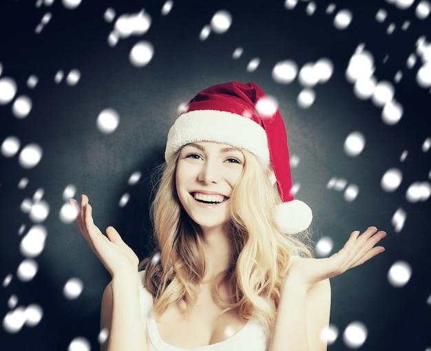 Christmas woman in santa hat having fun on snow background