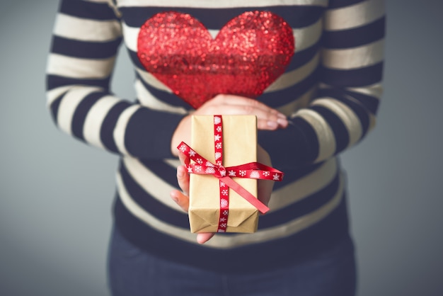 Christmas. a woman in a striped sweater with a red heart on her chest. woman with a christmas gift in hands