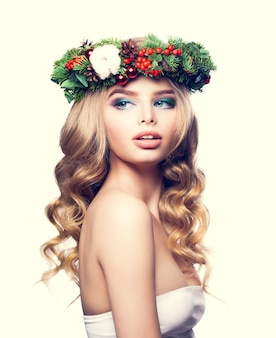 Christmas woman with makeup, blond curly hair and floral xmas wreath. young blonde beauty