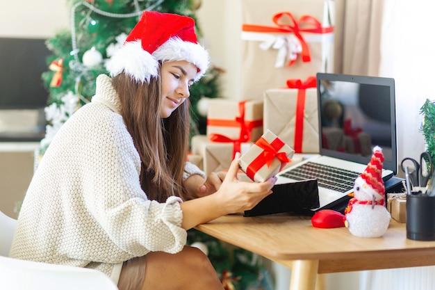 선물 상자가 있는 크리스마스 여자는 현재 상자 주변에서 인터넷 쇼핑을 하고 노트북을 보고 있습니다.