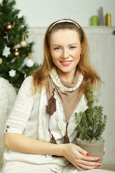 Christmas woman with xmas tree - smiling, happy and beautiful