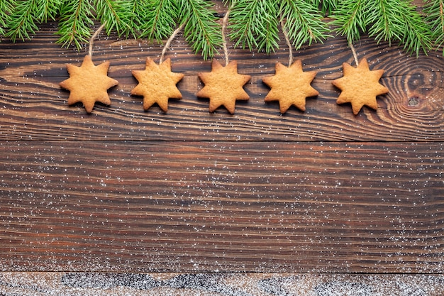 Christmas wood backdrop with homemade star-shaped biscuits hanging among fir branches
