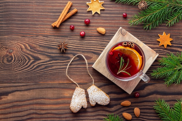 Christmas wooden backdrop with spruce branches and aroma spices and cookies and cup of tea