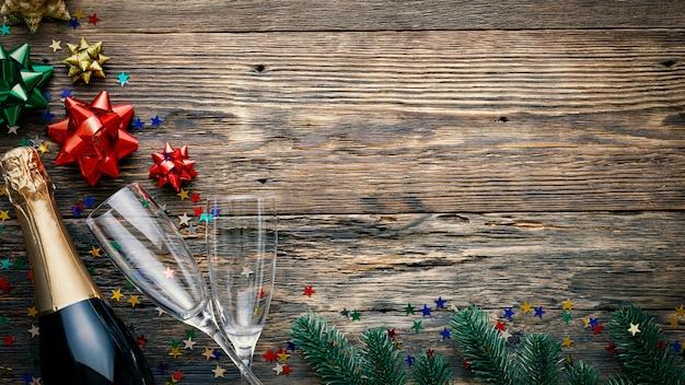 Рождественский деревянный фон, шампанское, бокалы и праздничный декор