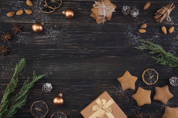 Рождественский деревянный фон с золотыми игрушками, подарком, печеньем, ветками можжевельника и орехами.