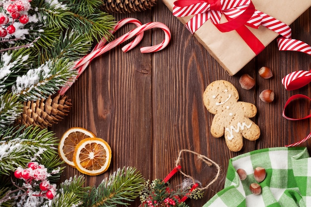 Christmas wooden background with snow fir tree, decor and gift box