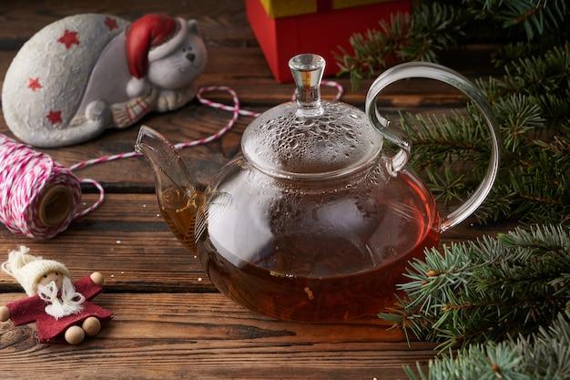 おもちゃ、装飾、ホットティーとモミの枝のティーポットとクリスマスの木製の背景。クリスマスのコンセプト
