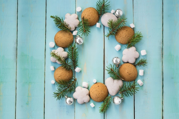 Christmas wooden background with tree branches, gingerbread and marshmallows