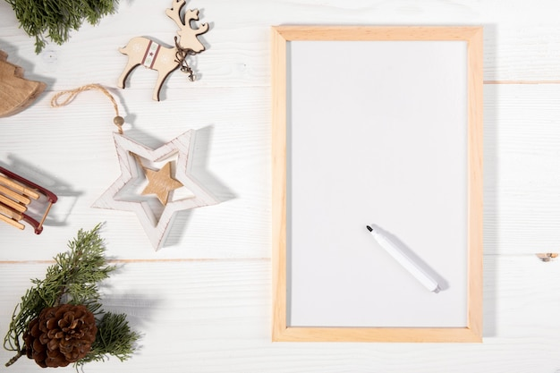 Christmas wooden decoration with christmas fir tree and white chalkboard notebook with with list