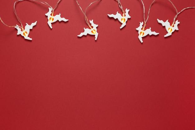 Рождественская деревянная гирлянда с теплым светом в виде белых бегущих оленей на темно-красной стене. праздничная новогодняя концепция. горизонтальная, плоская планировка. минималистичный простой стиль.