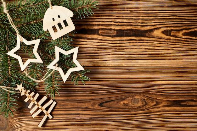 クリスマスの木製の星新年の木と木製の背景にモミの枝を持つ家