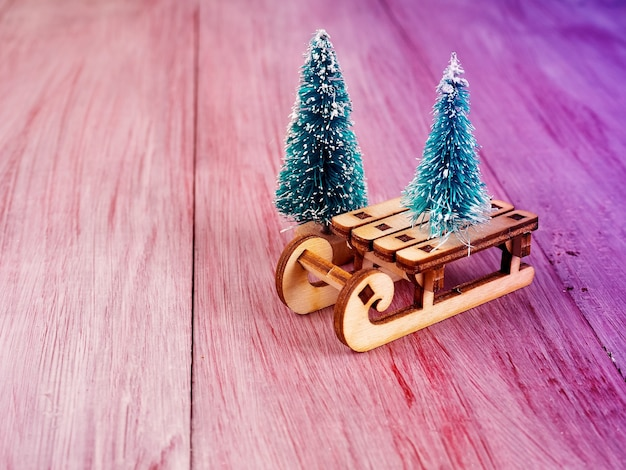 Christmas wooden toy sleigh and small christmas tree nearby, christmas concept, minimalism, place for text.