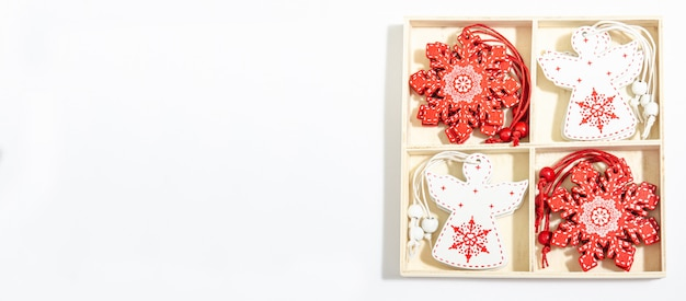 Игрушки рождества деревянные в форме белого ангела и красной снежинки в деревянной коробке для декора с местом для космоса экземпляра с положением квартиры на белой предпосылке.