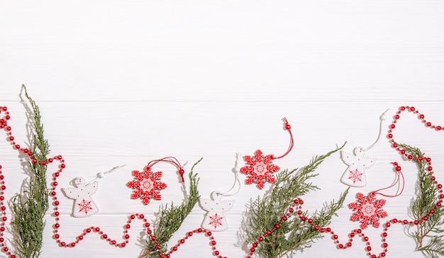 Рождественские деревянные игрушки в виде белого ангела и красной снежинки, красных бусин и ветвей можжевельника с пространством для копирования, пространство с плоским положением на белом фоне.