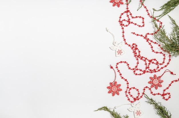 Рождественские деревянные игрушки в виде белого ангела и красной снежинки с можжевеловыми ветвями и красных бусин с пространством для копирования с плоским положением лежат на белом фоне.