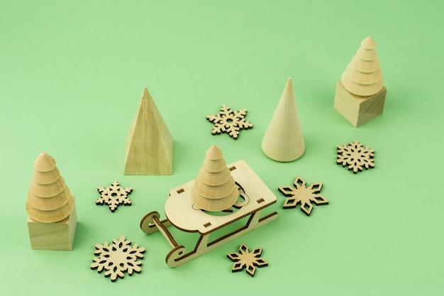 녹색 배경에 크리스마스 나무 장난감입니다. 녹색 배경에 친환경 나무, 눈 조각, 큐브, 썰매.