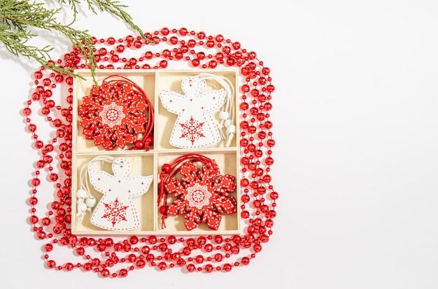 クリスマスの木のおもちゃ白い天使と木製の箱の赤い雪の結晶、赤いビーズ、白い背景の上のジュニパーの枝。コピースペース用のスペース、フラットレイ。上から見る