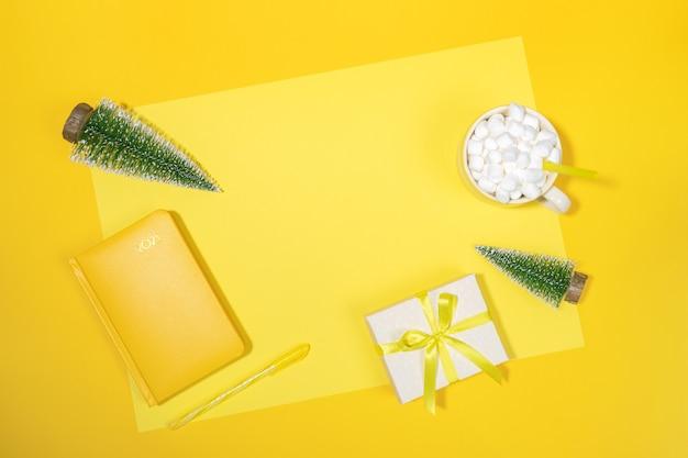 Рождественский фон рабочего пространства. желтый блокнот - органайзер на 2021 год, маленькие рождественские елки, чашка кофе с зефиром, подарочная коробка diy на желтом. подведение итогов, планирование. вид сверху, плоская планировка, копия пространства.