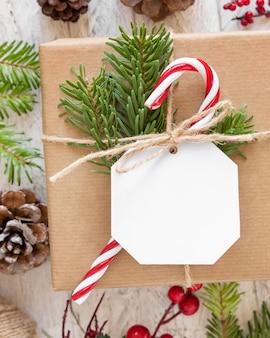 Рождественский обернутый подарок с бумажной подарочной биркой на белом столе с еловыми ветвями и украшениями. деревенская зимняя композиция с пустым подарочным тегом mockup, копией пространства