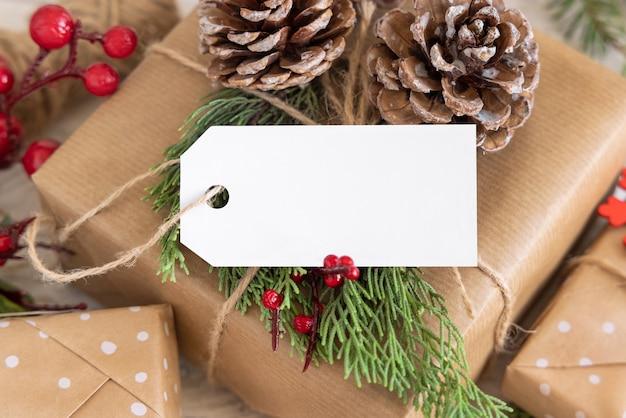 Рождественский обернутый подарок с бумажной подарочной биркой с еловыми ветками, сосновыми шишками и праздничными украшениями заделывают. деревенская зимняя композиция с пустой подарочной биркой, макет, копией пространства, крупным планом
