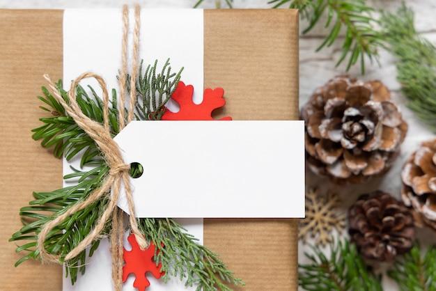 Рождественский обернутый подарок с бумажной подарочной биркой с еловыми ветками, сосновыми шишками и праздничными украшениями заделывают. деревенская зимняя композиция с пустой подарочной биркой mockup, копией пространства, плоской планировкой