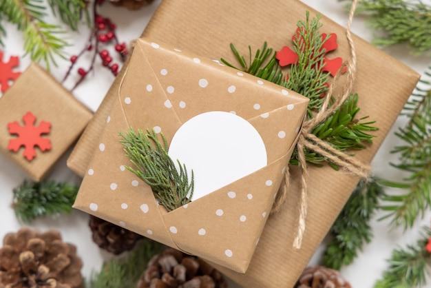 Рождественский обернутый подарок с круглой бумажной подарочной биркой с еловыми ветками, сосновыми шишками и праздничными украшениями заделывают. деревенская зимняя композиция с пустой подарочной биркой mockup, копией пространства, плоской планировкой