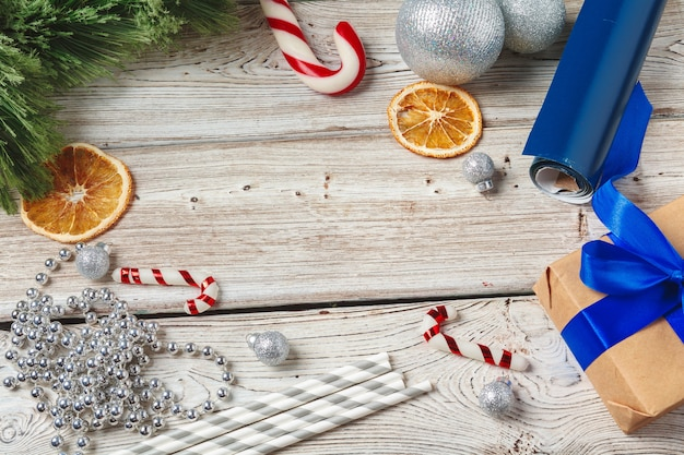 Christmas wrapping and decorating items on wooden background with copy space