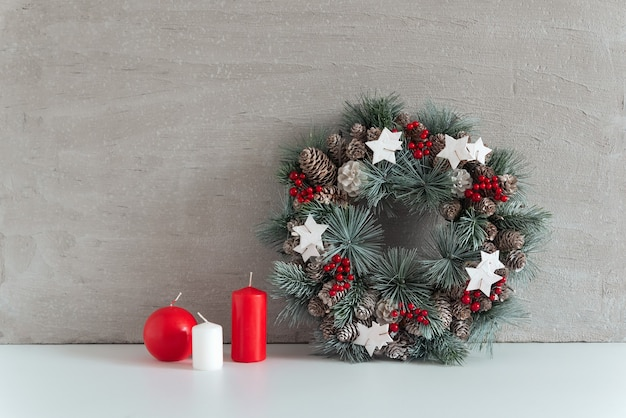 灰色の背景にクリスマスリースとキャンドル。居心地の良い休日の装飾。