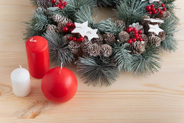 明るい木製の背景にクリスマスリースとキャンドル。クリスマスと新年のコンセプト。