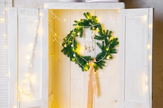Рождественский венок и гирлянда в деревянном шкафу или шкафу