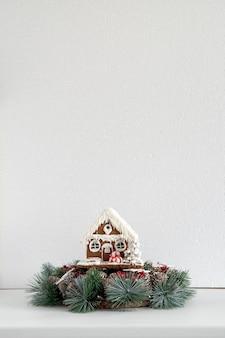 白い背景の上のクリスマスリースとジンジャーブレッドハウス。大晦日とクリスマス。スペースをコピーします。