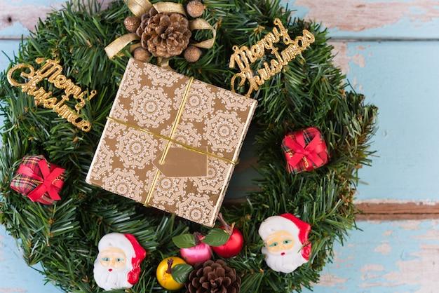 그런 지 푸른 나무 배경에 크리스마스 화 환 및 황금 복고풍 선물 상자 장식