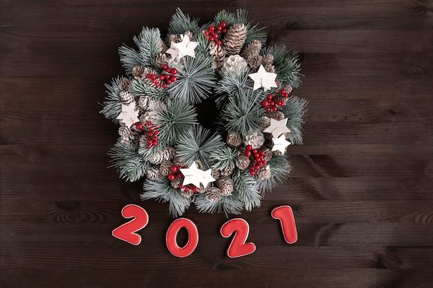 Рождественский венок и имбирное печенье с надписью 2021 на деревянном фоне.
