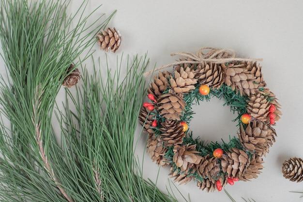 베이지 색 표면에 크리스마스 화 환과 pinecones