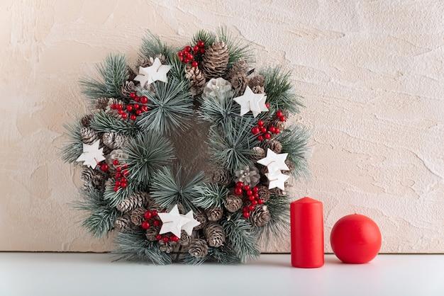 明るい背景にクリスマスリースと赤いキャンドル。クリスマスデコレーション構成。