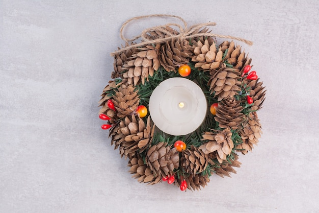 Christmas wreath and candle on white surface