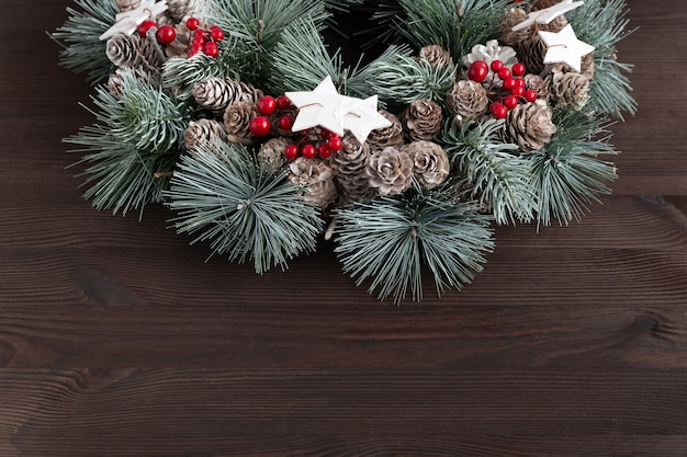Christmas wreath on dark wooden background. new year pattern. copy space.