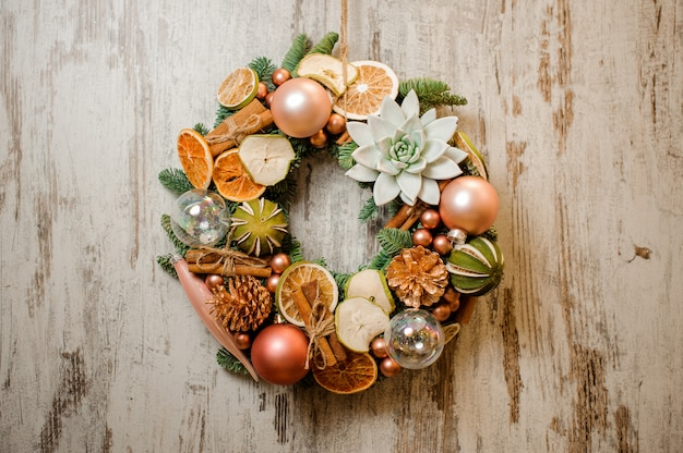 Christmas wreath decorated with dried oranges, cinnamon sticks, succulents and tree toys