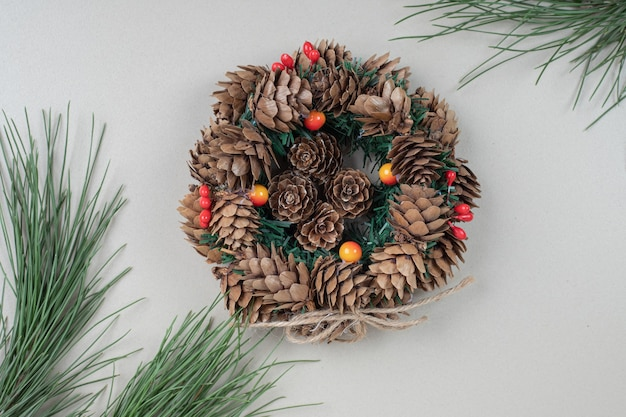 Christmas wreath decorated with pinecones and holly berries