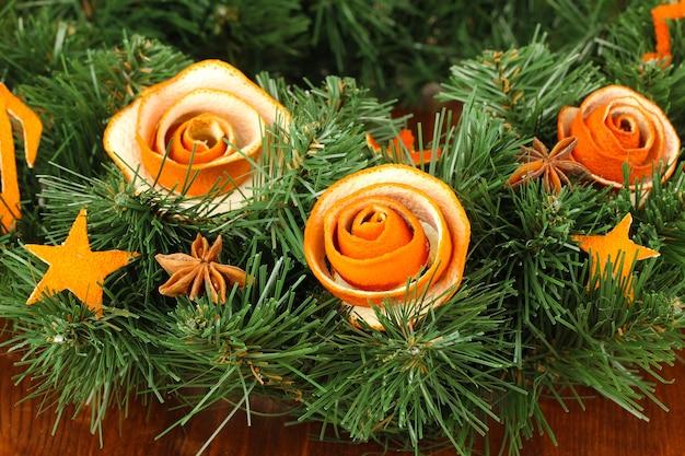 Рождественский венок, украшенный розой из сухой апельсиновой корки на деревянном столе