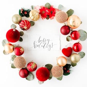 色付きの明るいクリスマスボールと白い背景の上の書道の言葉ハッピーホリデーで作られたクリスマスリースフレーム。