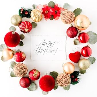 色付きの明るいクリスマスボールと白い背景の上の書道の言葉メリークリスマスで作られたクリスマスリースフレーム。
