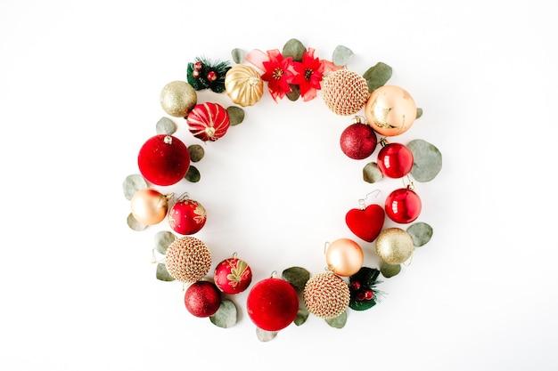 白い背景の上の色の明るいクリスマスボールで作られたクリスマスリースフレーム。