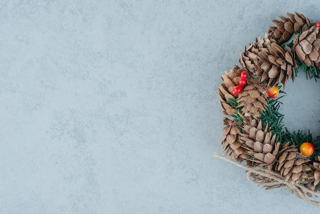 Una ghirlanda di natale da pigna su sfondo marmo. foto di alta qualità