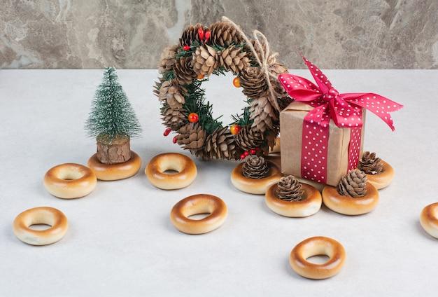 Рождественский венок из шишек с печеньем и небольшой подарочной коробкой. фото высокого качества