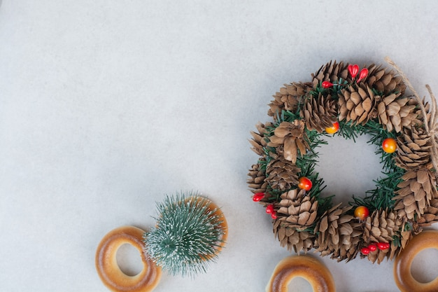 Christmas wreath from pinecones with cookies on white background high quality photo