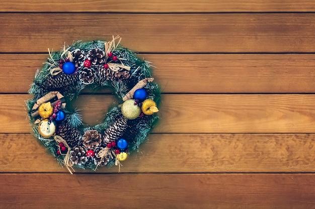 나무 배경에 수제 크리스마스 화환입니다. 화환의 축제 조명입니다. 새해 인테리어 장식. 텍스트를 위한 공간을 복사합니다.